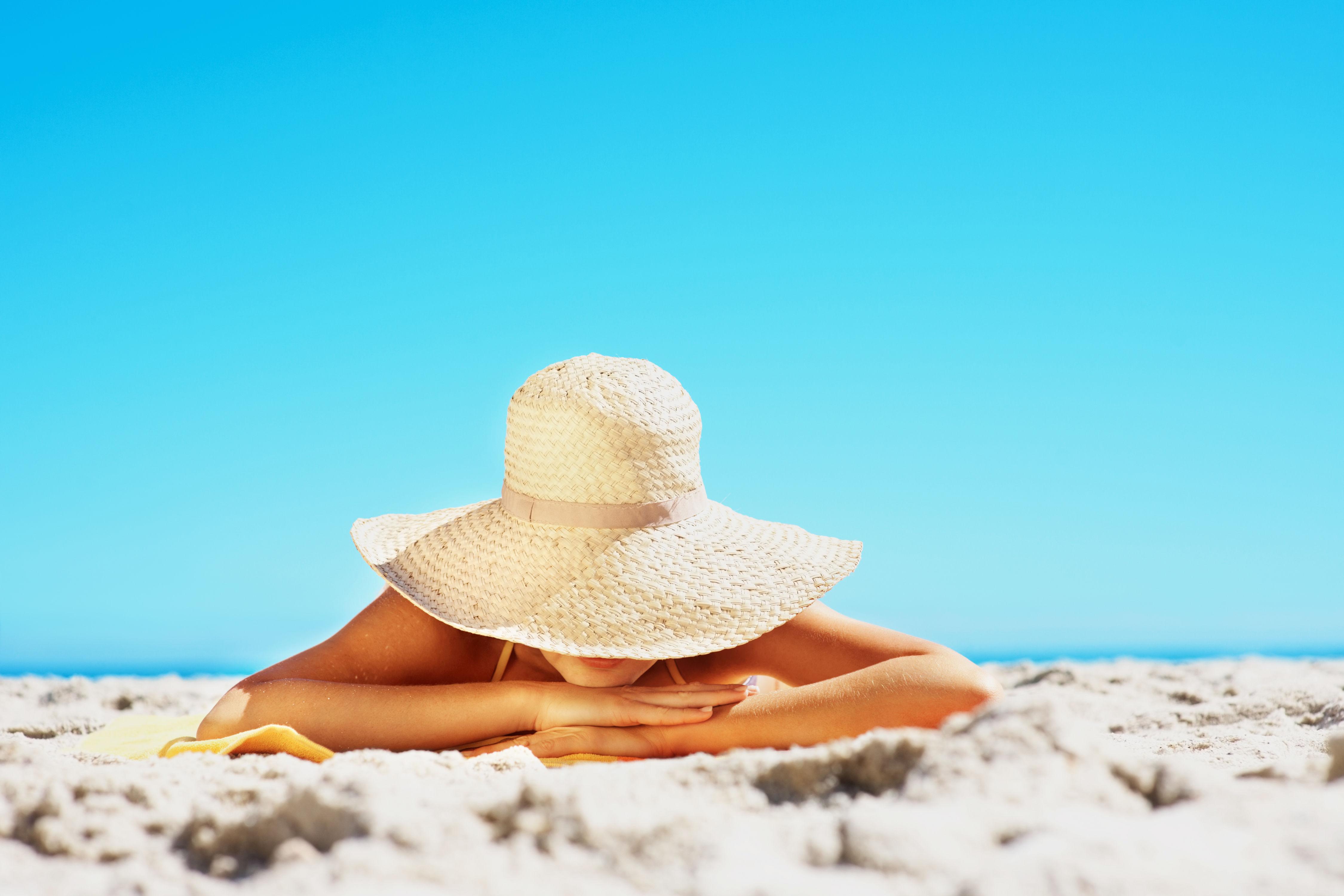 Woman Sun Bathing on Beach with Sun Hat