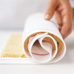 Roll the towel and the cake together, pressing gently. Be sure to move slowly and carefully throughout the entire rolling process. The towel will end up coiled inside the cake.