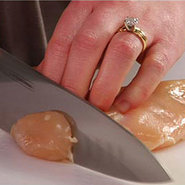A chicken breast being cut into strips