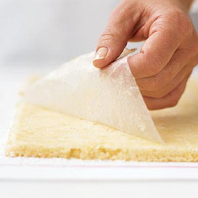 Remove the cake from the oven, and turn the pan over onto the towel, releasing the cake and wax paper. Slowly peel the wax paper from the cake. It's OK if a thin layer of cake remains on the paper.