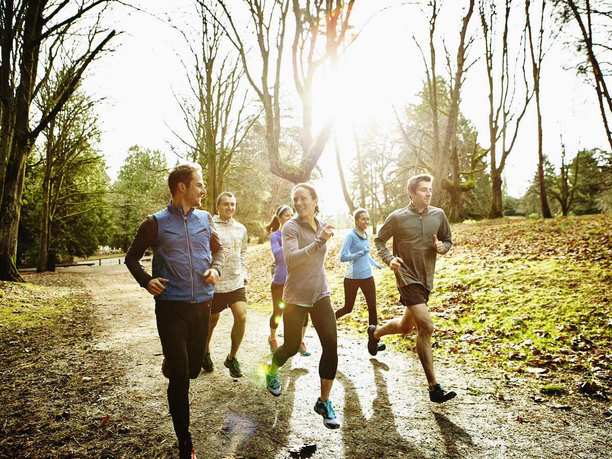 Smiling group of male and female runners trail running together in park