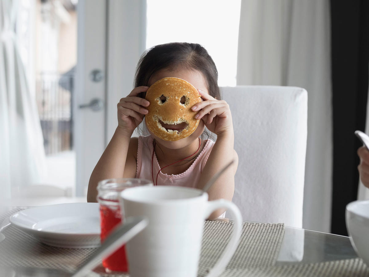 Girl holding smiley face pancake mask