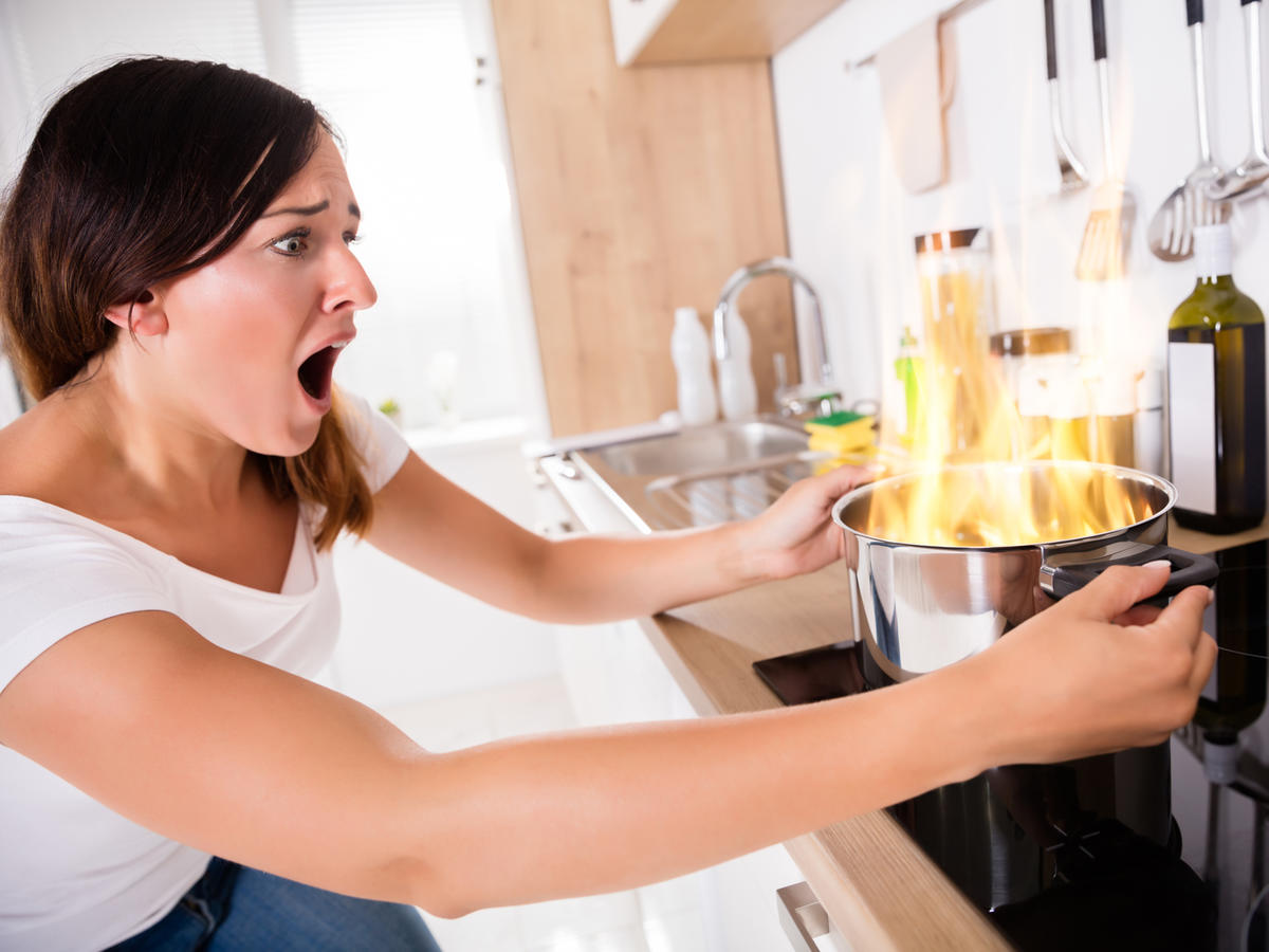 Shocked Woman Holding Pot on Fire
