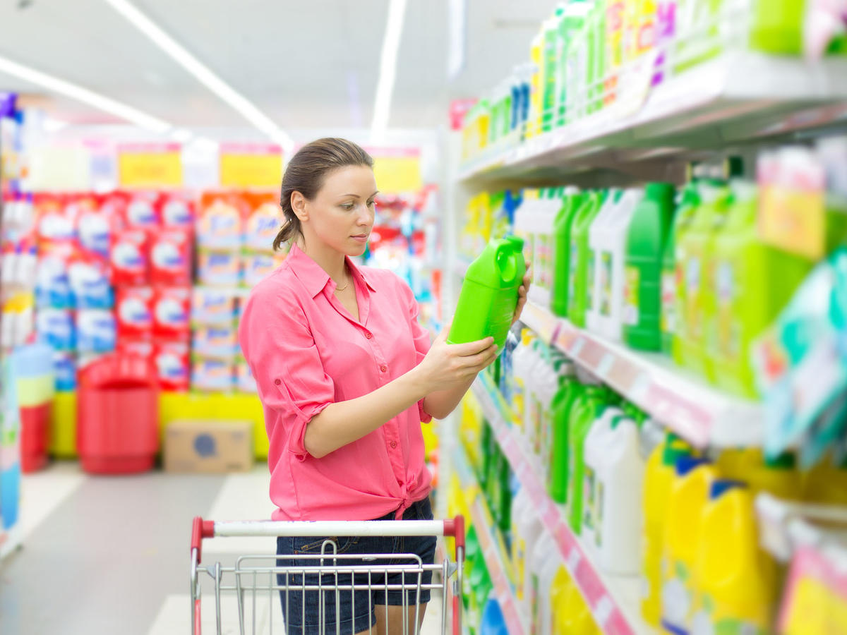 Woman checking cleaning product labels