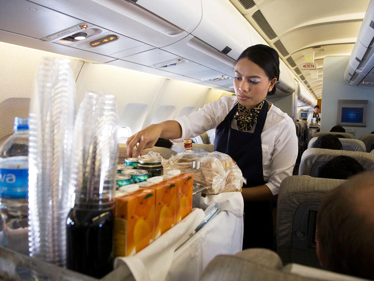 Cabin crew / air stewardess serves drinks to passengers from a beverage cart during a flight