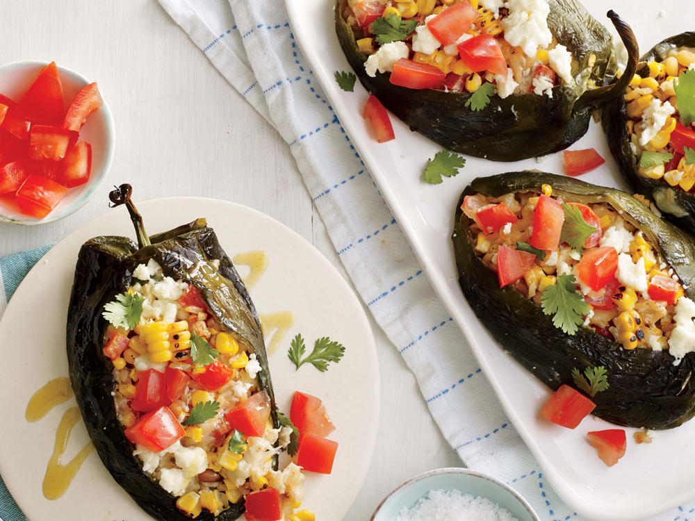 In this garden-inspired recipe, charred poblano chiles are stuffed with a delicious grilled corn and rice mixture. Before placing them in the oven, sprinkle with queso fresco and broil until golden. Serve with hot sauce, if desired.