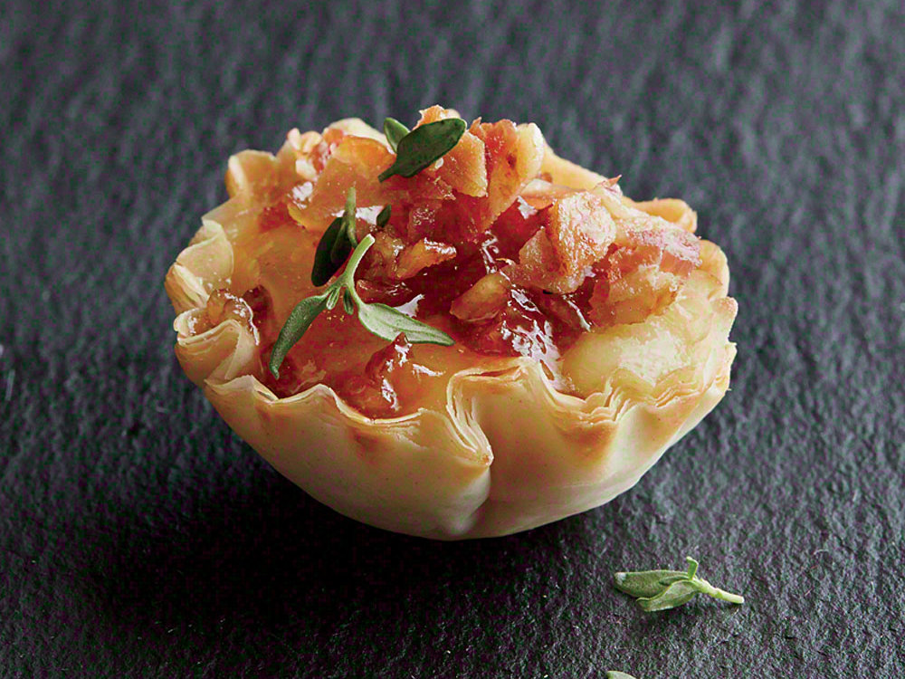 Perfect for a night of entertaining friends, these phyllo cups are overflowing with delicious melted Brie, crumbled bacon, and sweet apricot jam.