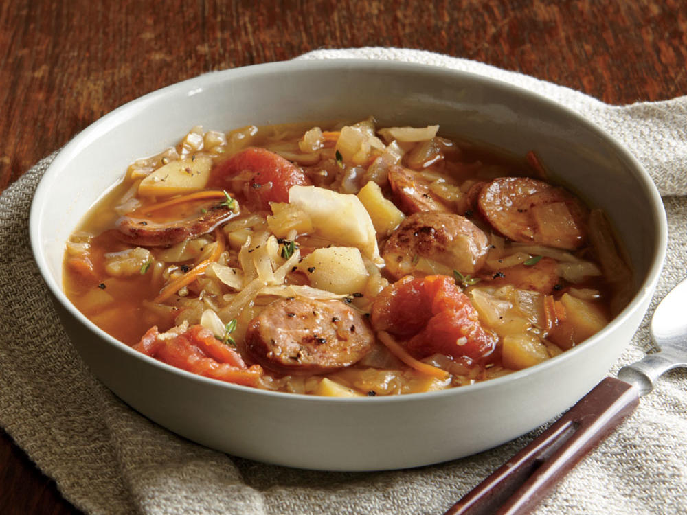Smoky andouille gives this hearty and comforting soup a wealth of deep flavor, while chopped coleslaw mix allows it to come together in a flash.