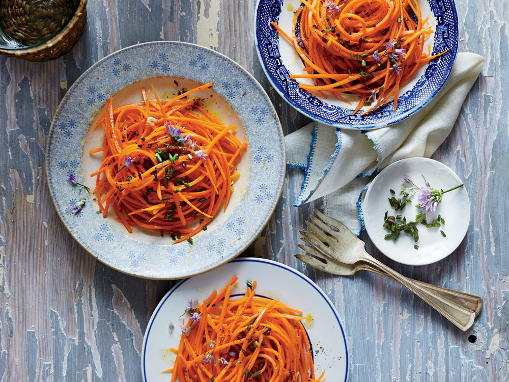 Raw carrots are cut in fine julienne, then dressed with a lemony vinaigrette with a hint of garlic. Before serving, the salad is showered with freshly cut chives (and chive blossoms, if you have some).