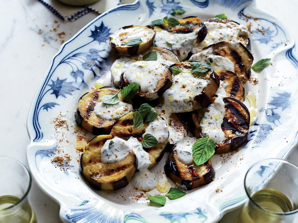 Cumin, coriander, cinnamon, and mint provide North African flavor for the tender grilled eggplant. A tangy spiced yogurt sauce complements each sweet and smoky slice.