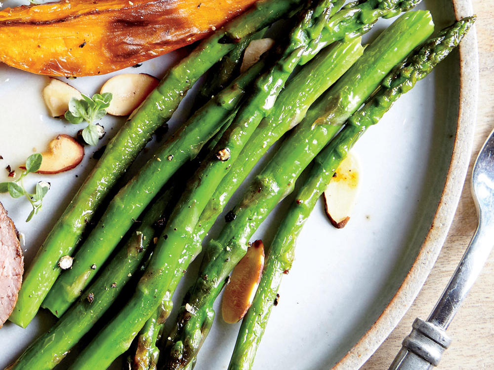 Olive oil, kosher salt, black pepper, and toasted almonds drizzled over asparagus create a simple but satisfying side.