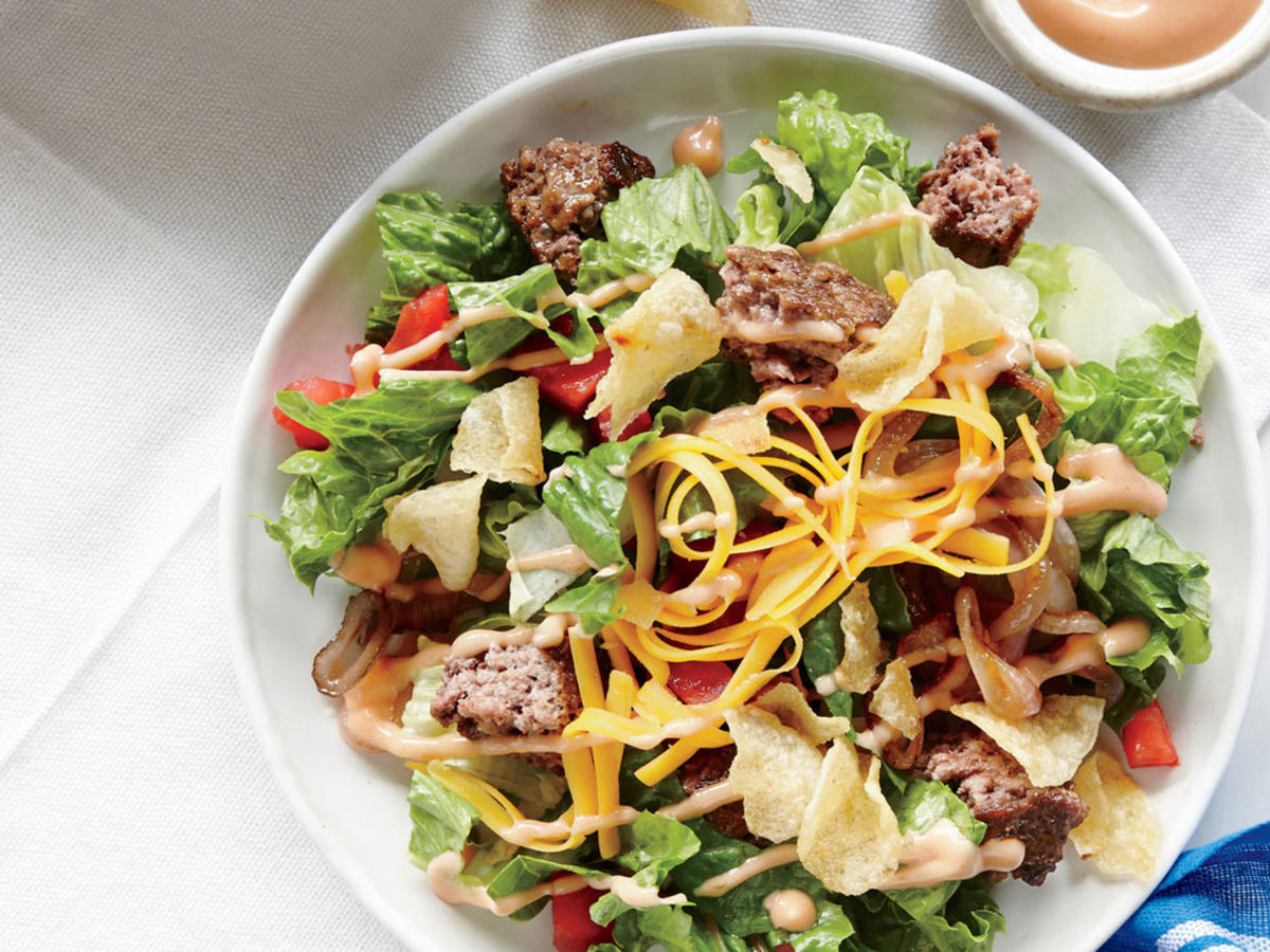 Classic burger elements become a fast, fun salad for the entire family—a deconstructed take on a diner favorite. Instead of four burger patties, we cook just two, then chop and sprinkle them over the top. A handful of crushed potato chips adds crunch. Kick up the dressing with a pinch of ground red pepper.