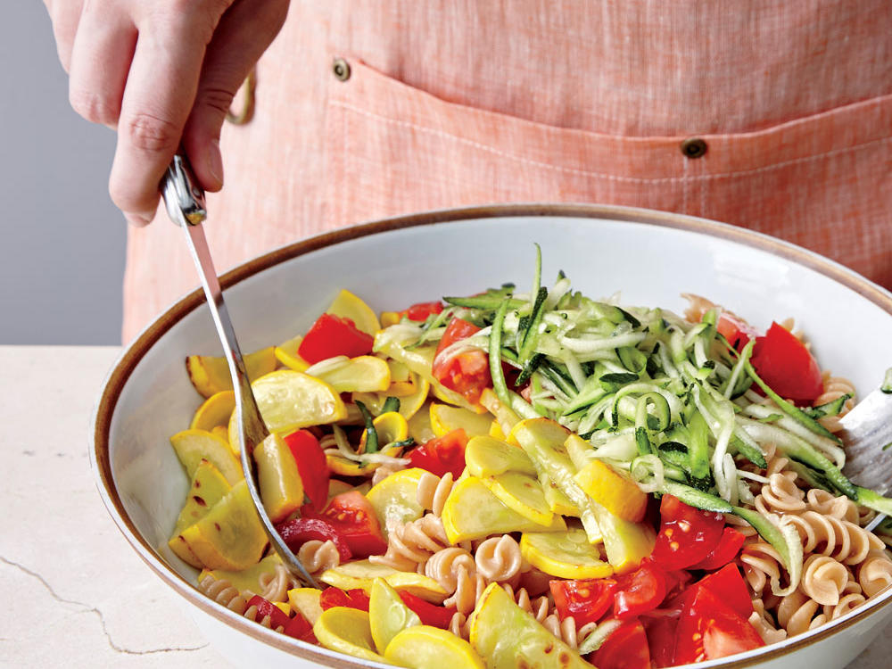 Grated zucchini will cook as the pasta is tossed. If you don't have a grater, cut the zucchini like the yellow squash, and sauté both.