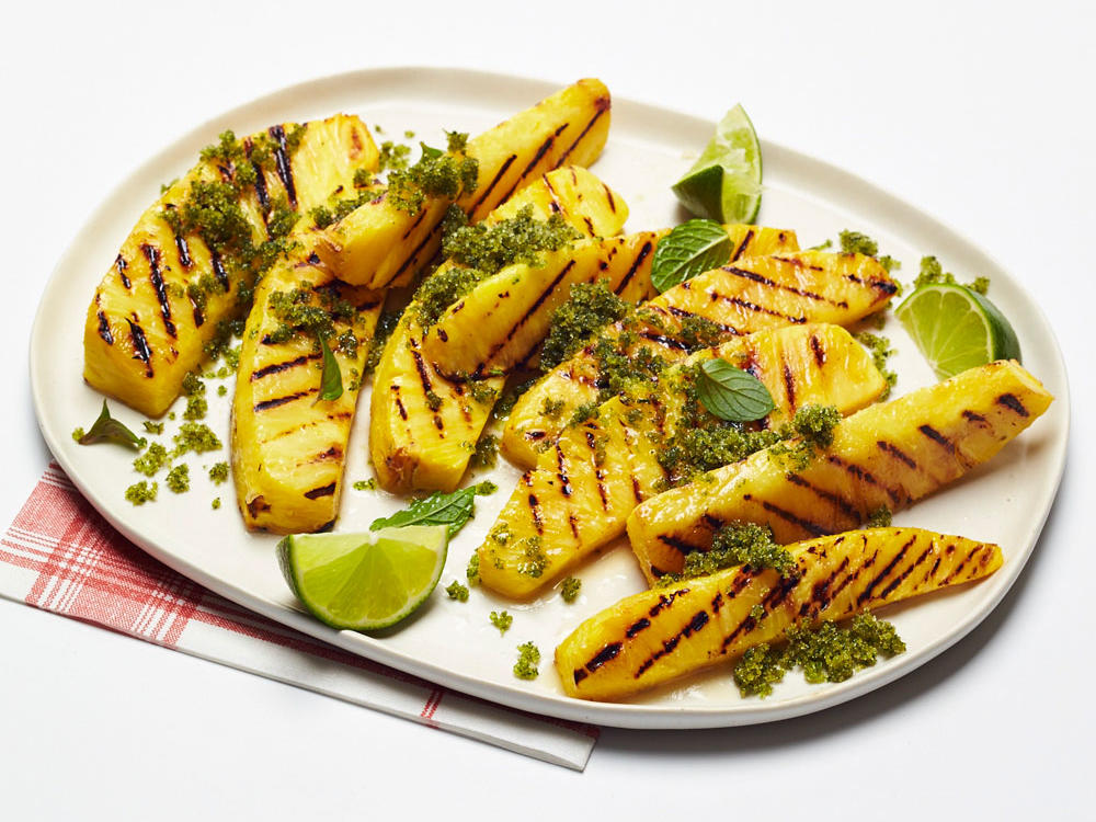 Chargrilled pineapple slices caramelize and become extra juicy, a worthy dessert on their own. Go one step further with a generous sprinkle of mint-lime sugar—it adds an incredible fragrance and a bit of crunch to every bite. This is delicious on its own or served with low-fat vanilla ice cream. This simple 3-ingredient dessert can be thrown together in less than 20 minutes and gives you the sweetness you crave without a lot of fat, calories, or added sugar. It's the perfect vegetarian dessert for hot summer days or for those on a diet.