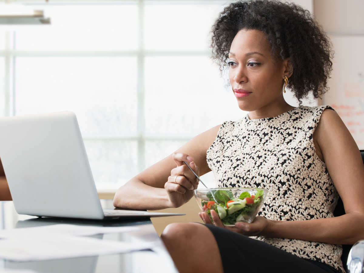 Woman Eating Salad at Computer Getty