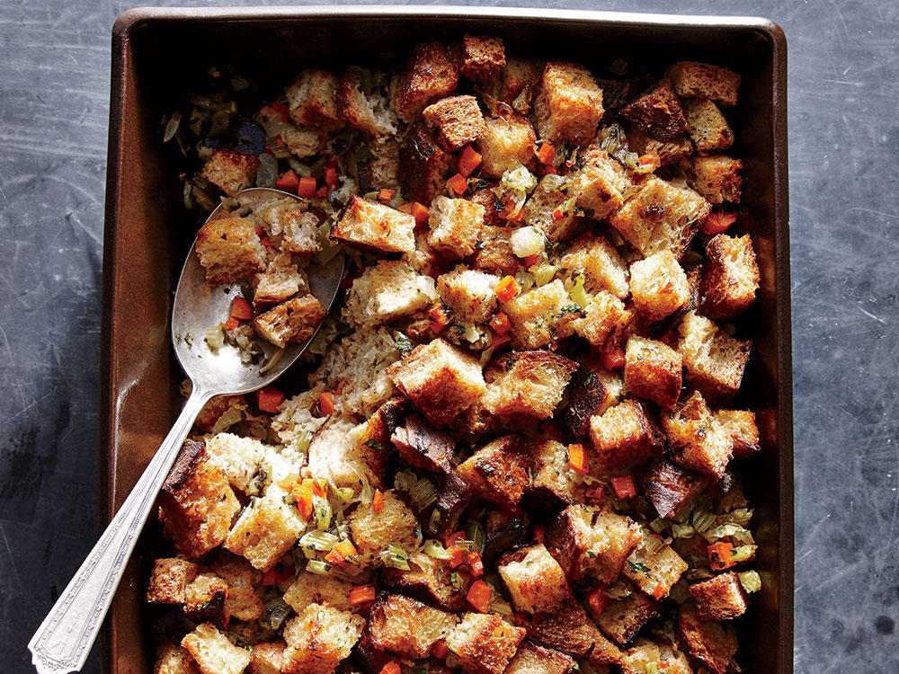 A straightforward holiday stuffing calls for great bread; we love the nutty toasty dimension of a bakery whole-grain loaf. Sauté the onion, celery, and carrot mixture until tender but not browned. The added moisture from the veg will help soften the bread and make for a more cohesive stuffing. Combine the wet and dry ingredients in a bowl rather than a baking dish for more even coverage, and let the mixture stand a few minutes before baking. The bread will soak up the eggy liquid like a sponge so nothing is left behind.