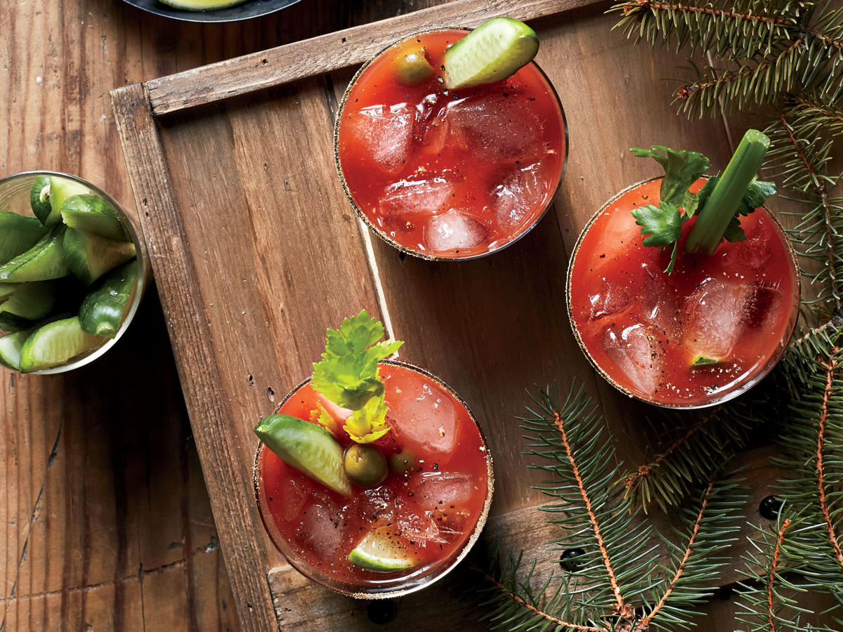 "Kick off your festivities with this fun take on the classic brunch beverage. Molly likes to boost her version with harissa, a traditional Tunisian chile paste with a spicy, pleasantly bitter edge. ""I just love those flavors,"" she explains, ""and they're not common around Grand Forks, North Dakota. I really like being able to introduce a new ingredient like harissa to my community through a more familiar thing like a Bloody Mary."" Look for harissa in cans, jars, or tubes on the international foods aisle or with the specialty sauces. If you can't find it, substitute a few dashes of hot sauce. Garnish as desired with celery stalks, lime wedges, and pickles. You can combine everything except the club soda a day ahead; give it a good stir before serving, and top off with club soda at the last minute."