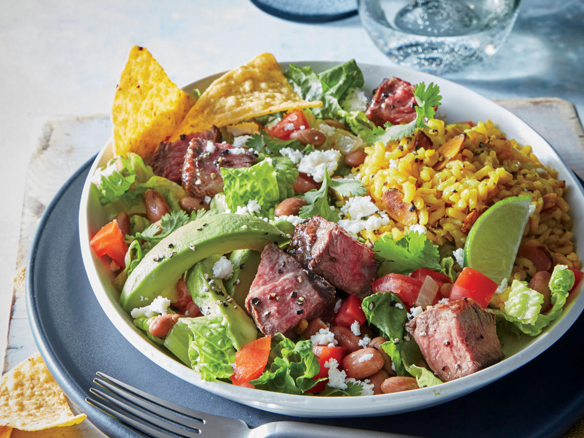 This gluten-free take on a taco salad uses seared flank steak in place of ground beef. Instead of a fried tortilla shell, crisp romaine lettuce forms the sturdy base for each salad with crunchy tortilla chips crumbled on top. Queso fresco is a firm, mild cheese—a great alternative to feta if you're not a fan of the tang. Use as your go-to cheese for Mexican egg scrambles, burritos, or stuffed chiles. Keep the tortilla chips whole for scooping, or lightly crush them and sprinkle on top. Serve over Cilantro and Almond Pilaf.