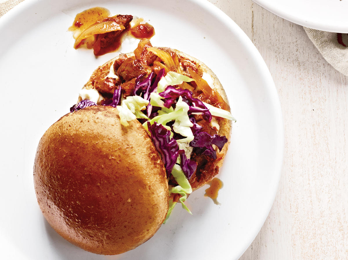 These pork sandwiches are a nod to low-and-slow Southern barbecue–using just a little bit of pork shoulder. And just like traditional pulled pork, the meltingly tender vegetables and pork are piled high on toasted buns, slathered with a Greek yogurt mixture, and topped with shredded cabbage.