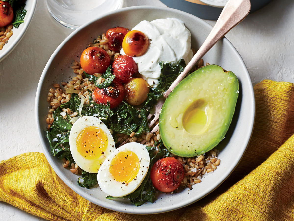 This meal in a bowl takes its morning cue from soft-boiled eggs and a dollop of yogurt, and then goes savory with toasty cumin-scented farro and a creamy avocado. It's also perfectly portioned for two. Boil the farro like pasta—in plenty of water that you'll drain off—to cut the cook time in half. Toasting the farro in a little oil is a great way to revive any leftover cooked whole grains. Whole-milk Greek yogurt has a cool, luxurious mouthfeel that brings all the elements together. It also has more protein than reduced- or nonfat yogurt. Add Blistered Tomatoes with Kale on top for a final touch of veg.