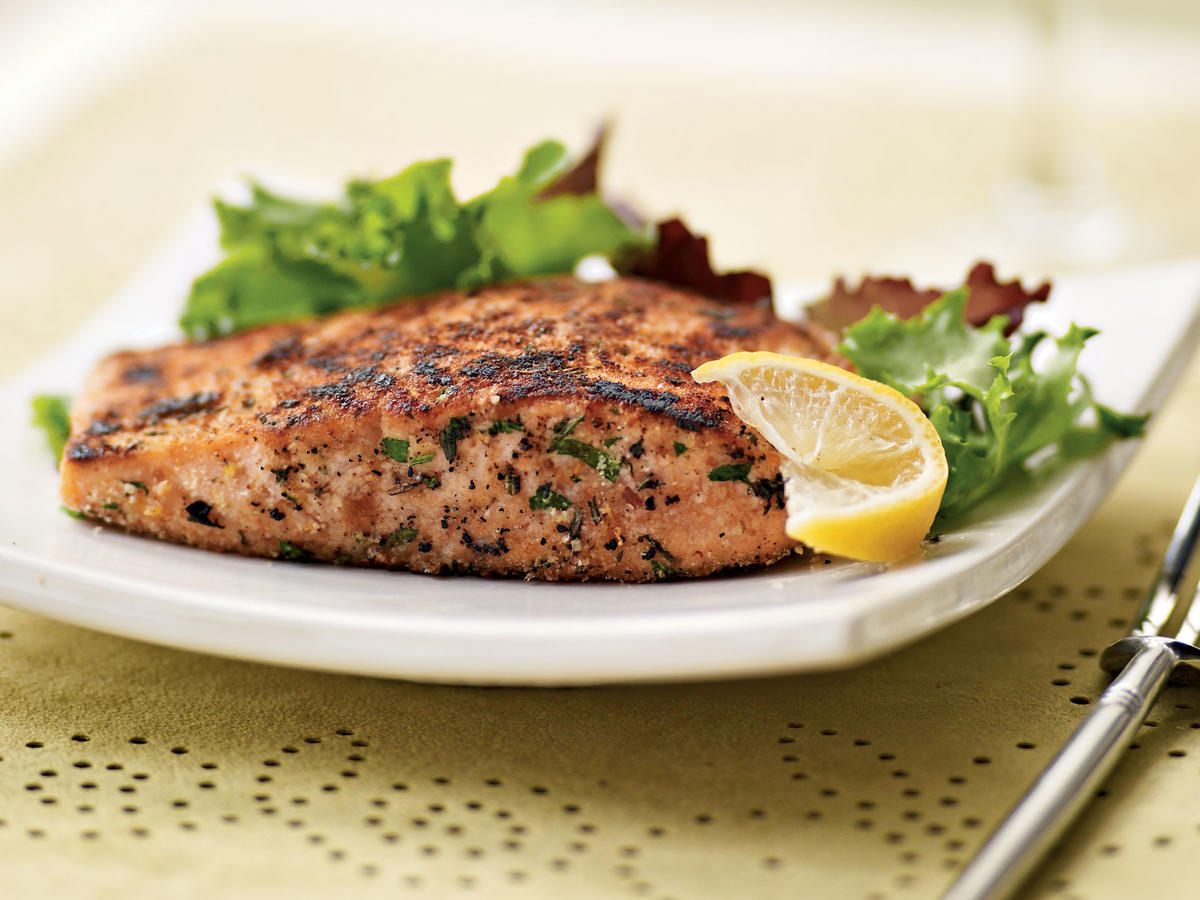 Chopped fresh herbs dress up salmon fillets, which are a great source of heart-healthy omega-3 fatty acids. The homemade vinaigrette brightens salad greens while keeping calories and fat in check. Serve salmon with lemon wedges.