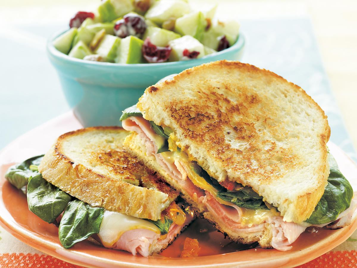 Mild Muenster cheese is too often overlooked; it's great for sandwiches, burgers, omelets, or just plain snacking. It matches well with thinly sliced ham, fresh spinach, and sweet-and-tangy chowchow in these crusty-breaded sandwiches.