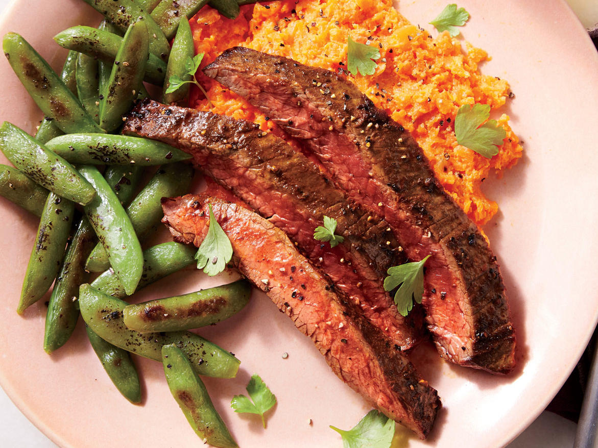 Steak, peas, and carrots are a familiar trio, and usually not very exciting. Here, each element is transformed: a smoky spice rub on seared flank steak, crispy snap peas brightened with rice vinegar, and a silky carrot mash. Chop the carrots to about 1/4-inch pieces so they cook through evenly, otherwise the mash may have a few lumps. The grain of the meat refers to the direction of the muscle fibers (in flank steak, they run lengthwise). Cut across the grain, or across the width of the steak, to break up the fibers for slices that are tender, not tough.