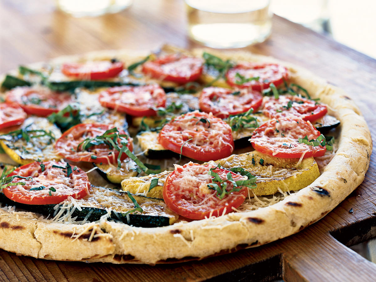 Healthful and abundant squash and zucchini get the family-friendly pizza treatment here. A balsamic marinade makes the squash extra sweet, then it's grilled, along with the pizza crust itself, for lots of smoky, charred flavor. A topping of tomatoes, pecorino cheese, and herbs finishes it all off.
