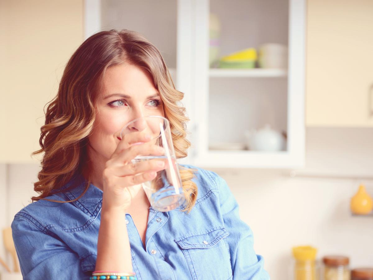 Woman in Kitchen Drinking Water