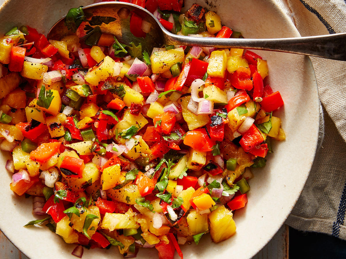 Sweet and smoky grilled pineapple combines with peppers and onions for an brightly colored salsa that deserves a spot at your next cookout.