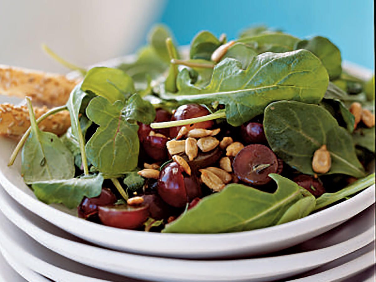 "Super clean salads highlight all kinds of fresh, wholesome, unprocessed foods, like vegetables, fruits, whole grains, and more. This one features spicy arugula, sweet red grapes, and another clean eating staple, sunflower seeds. Seeds and nuts are a common ingredient in ""clean"" cooking because they fill you up, provide hard-to-get nutrients like magnesium, zinc, selenium, and vitamin E, and are chock full of good fats.