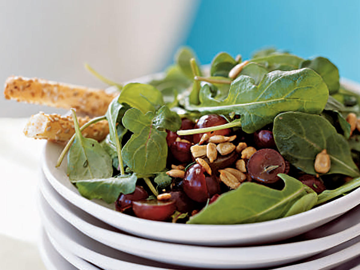 By including a variety of ingredients, salads are often a nutritional powerhouse: This recipe provides lots of antioxidants from the grapes, healthy fats and vitamin E from the sunflower seeds and grapeseed oil, and folate and vitamin A from the arugula. A sweet mustard vinaigrette dressing matches both the peppery bitterness of the greens and the sweet juiciness of the grapes. Try this salad topped with salmon or tuna for a healthful dinner.