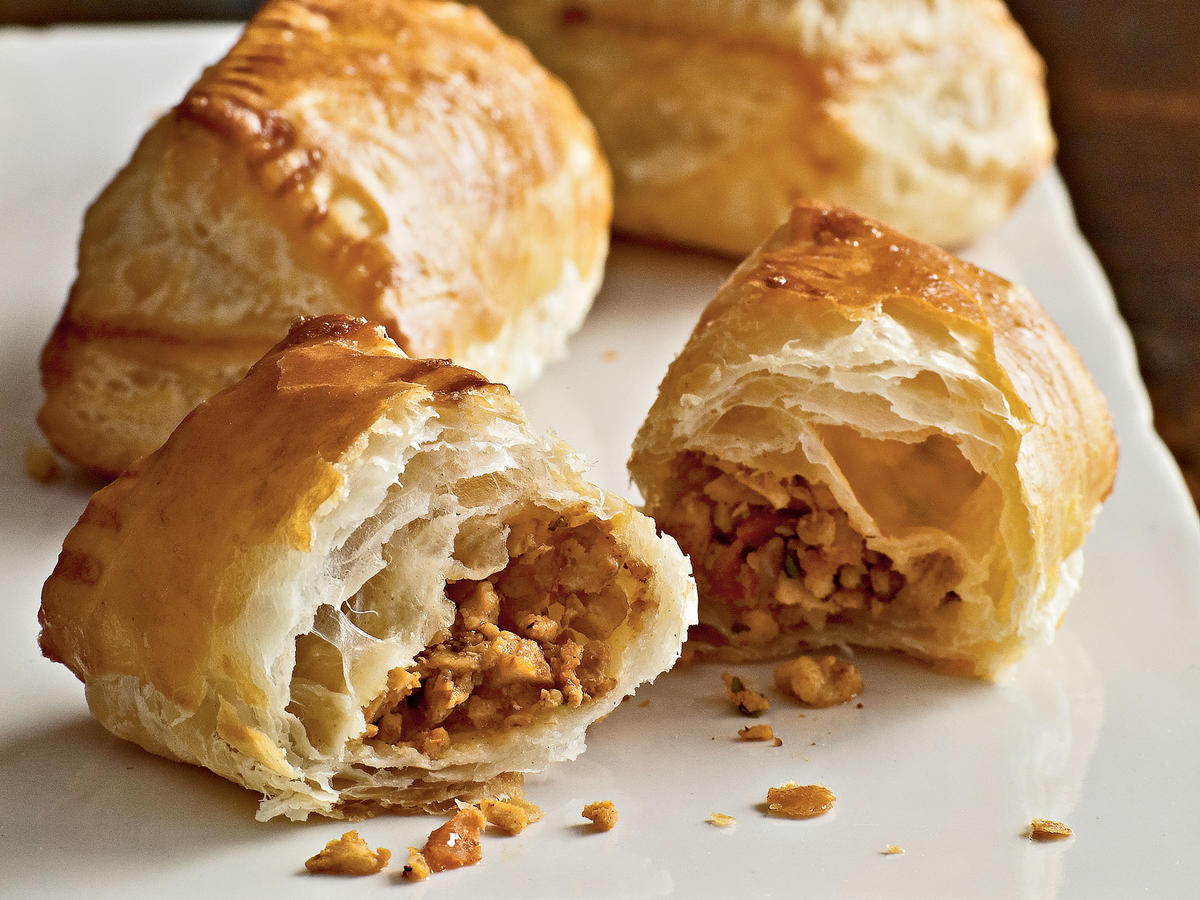 We fill flaky puff pastry with a picadillo—a spicy, aromatic minced hash that is popular in Mexico, the Philippines, and countries in the Caribbean—for an easy appetizer guests won't soon forget. Picadillos are traditionally loose and saucy, meant to be stuffed into bell peppers and served over rice. By cooking the mixture first, cooling it, and mincing in the food processor, we get rid of excess moisture and create a cohesive filling that won't spill out of the puff pastry pockets. Serve this dish at gatherings that call for more substantial appetizers.