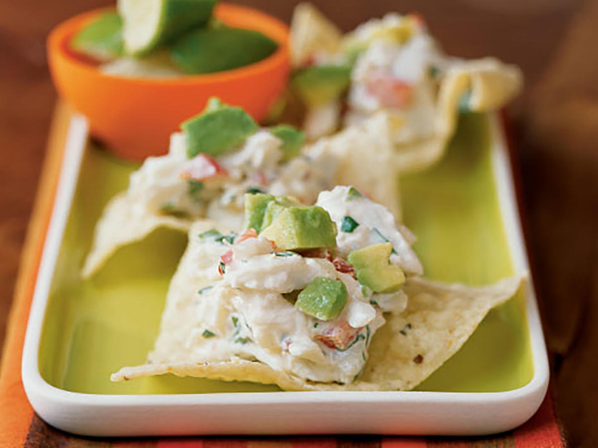 This easy crab salad that has tons of flavor―tangy lime, fiery chipotle, creamy avocado, and crunchy vegetables―is baked on tortilla chips for a unique appetizer. Lump crabmeat is pricey, but this dish makes the most of just 3/4 pound to serve 16 by mixing it with various veggies that add color, texture, and fresh flavor. A little avocado doubles down on the richness of the app. The chipotle is just enough to add a faint hint of smoke and spice without overpowering the delicately sweet crab. Keep leftover chipotles in adobo frozen for up to 6 months. A good way to store them is to ladle them into ice cube trays or onto a parchment-lined sheet pan in tablespoons, place in the freezer until solid, then transfer cubes to a ziplock plastic bag, seal, and freeze. This way, you can use small portions (a little goes a long way) as needed, without thawing the entire batch.