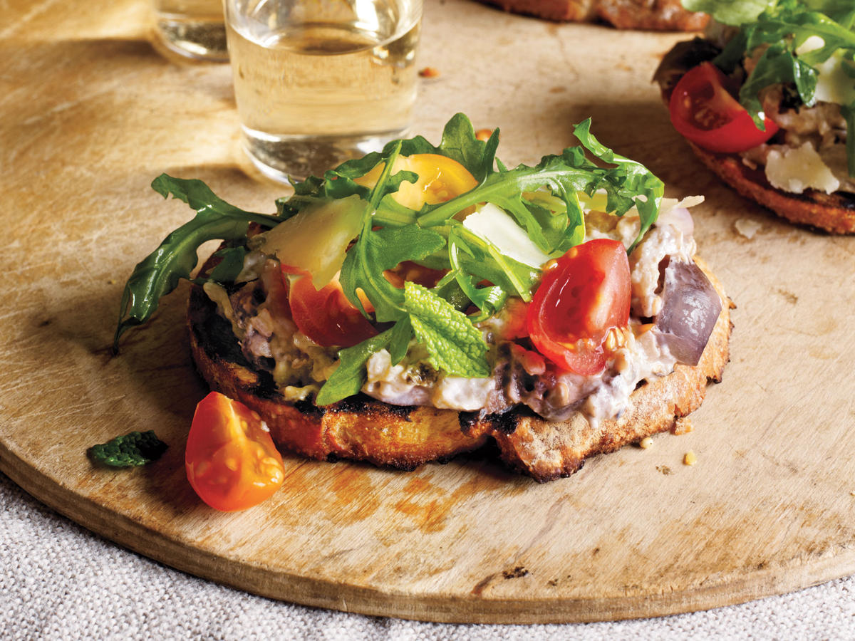 "Here's an elegant toast that makes the most of gorgeous farmers market produce. Grilled eggplant slices are pulsed in a food processor with lemon juice, full-fat Greek yogurt, and garlic—transforming into a spread for grilled baguette that has deep, rich, ""meaty"" flavor. A salad of colorful cherry tomatoes and arugula goes on top, so that your palate is first met with a burst of vibrant, fresh, sweet-tart flavor that then gives way to the richness of the eggplant. Once you've tried it, you'll keep this recipe in your back pocket for times you have guests you want to impress."