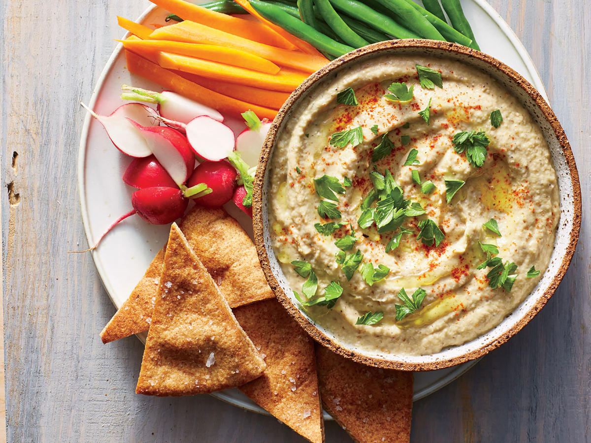 One of our readers, Karen Waldman, was dissatisfied with the baba ghanoush recipes she was finding, so she created her own. By combining mayonnaise and tahini, she tinkered, found her perfect combination, and even incorporated it into a Greek-themed Thanksgiving meal. The unique dinner was an instant hit with her family. Toasting the nuts and cumin seeds brings out their oils and magnifies their flavor. A little tahini—sesame seed paste—adds creaminess and a pleasant touch of savory bitterness. The mayonnaise lends even more creaminess to the roasted pureed eggplant. Garlic fans may want to double or even triple the amount in the recipe. This dip is perfect for toasted pita chips or even with raw veggie crudités.