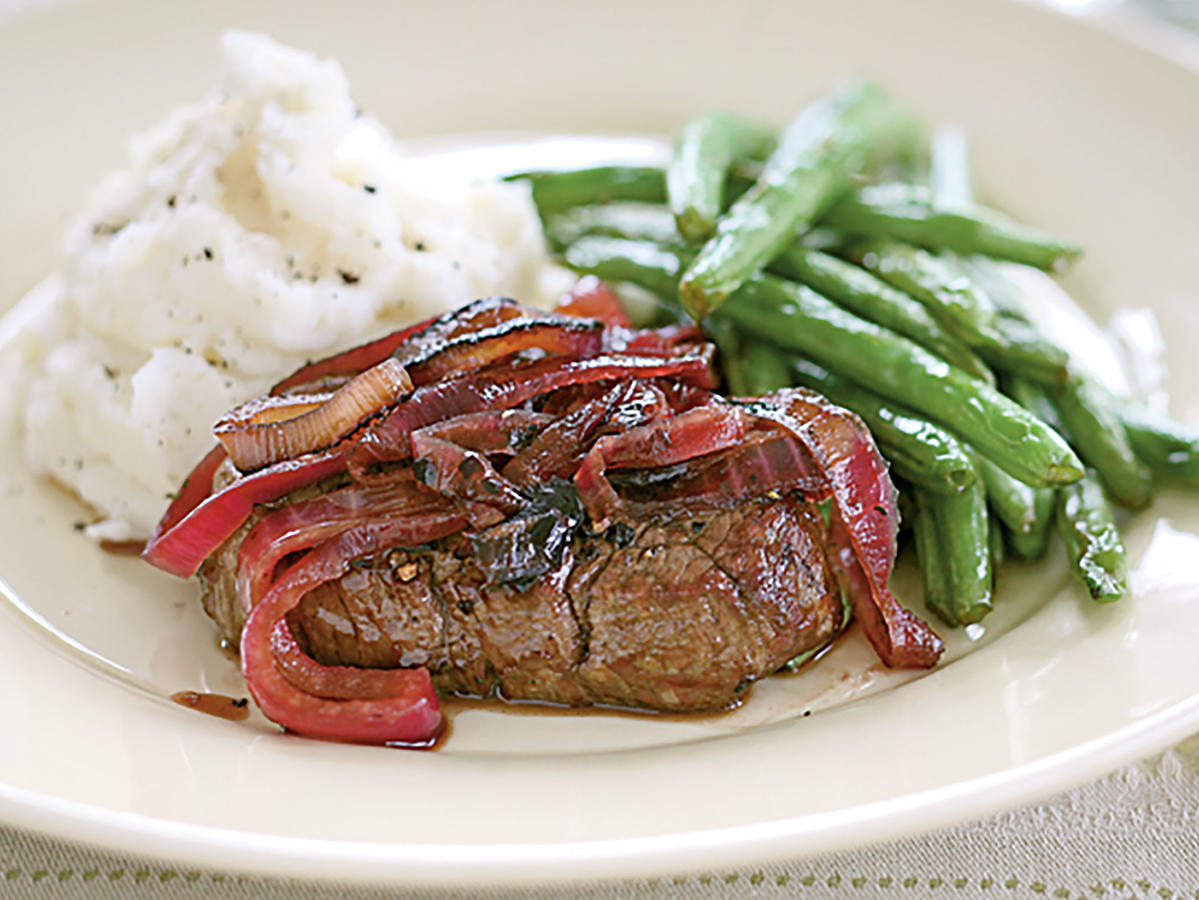 "Simple, high quality ingredients are the key to putting nutritious, ""clean"" meals on the table fast. In this recipe, lean steaks are quickly broiled, then topped with sweet and sour onions. Beef tenderloin is naturally high in protein and is a good source of iron, B12, B6, and niacin. Small amounts of protein eaten throughout the day build lean muscle mass, promote satiety, and keep blood glucose levels stable so you don't feel sluggish. Pair with steamed green beans and smashed potatoes for a family-pleased meal you can feel good about."