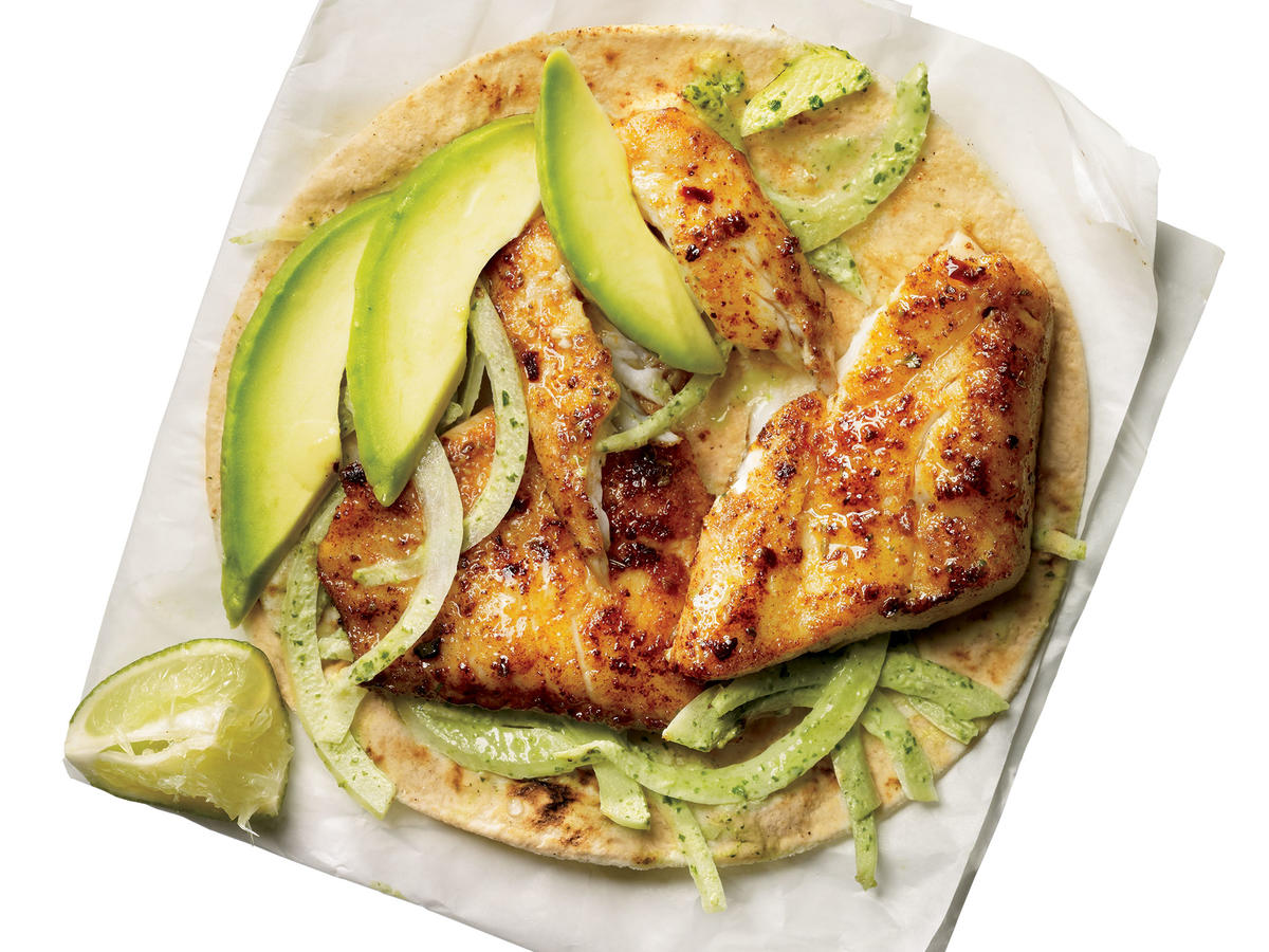 Make food truck-style fish tacos at home using fresh tilapia, avocado, cilantro, and corn tortillas; top with a creamy onion-jalapeño mixture for amazing flavor.