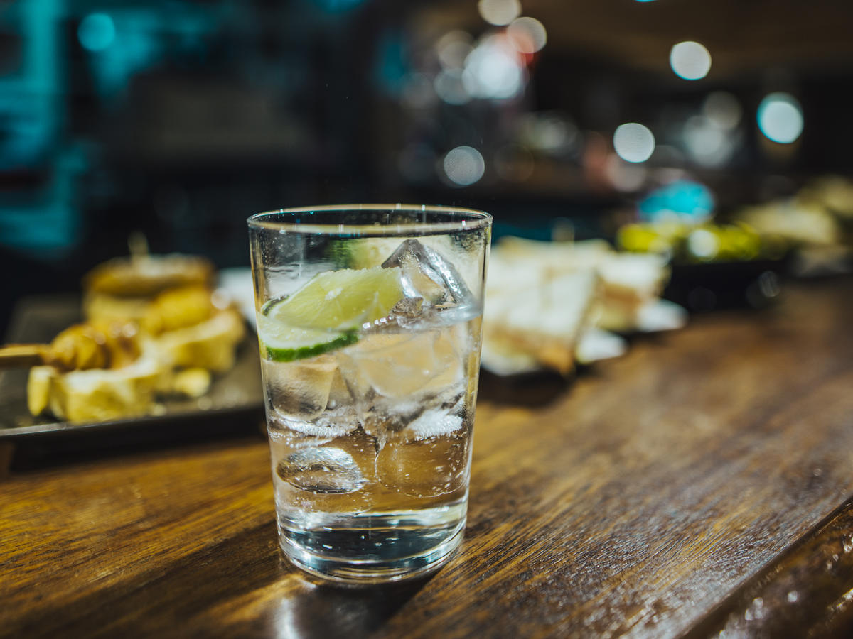 Glass of gin and tonic on a wooden bar