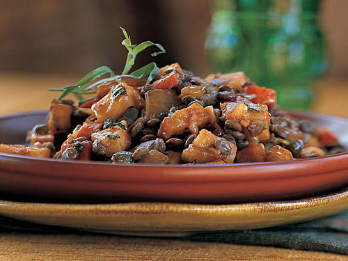 Winter vegetables are cooked separately, glazed with tomato paste and red wine, and then added to the lentils. Any lentils will work, but we like black or French green lentils for this recipe; they make for the most dramatic presentation and have a great flavor.