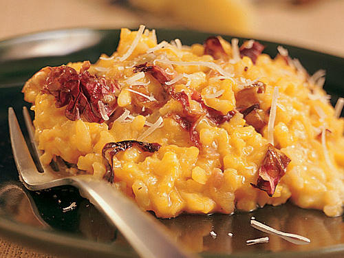 Golden winter squash adds color to this rich risotto.  The bitterness of radicchio is offset by the sweetness of the squash, and a shaving of earthy Parmesan cheese rounds out this festive side.