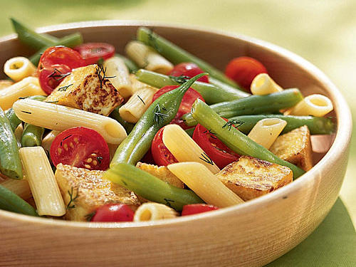 A light vinaigrette tossed with pasta, fresh summer produce, and sautéed tofu make this salad a hit for vegetarians and meat-lovers alike.