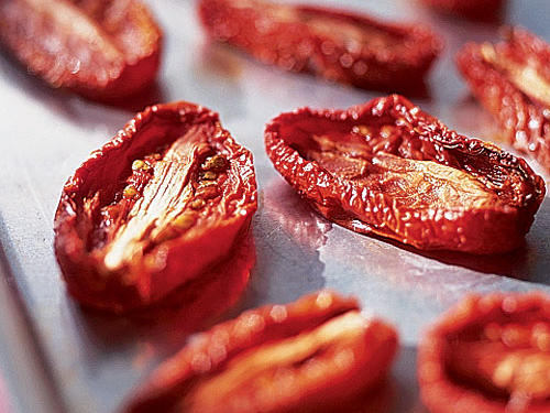 Summer tomatoes may need little help, but the oven-drying process greatly improves the quality of winter tomatoes. The concentrated flavor that results from cooking tomatoes at a low temperature for a long time provides instant richness and depth to a meal.