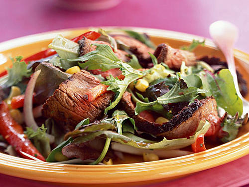 Opposites attract in this dish: hot steak sits atop cold salad, and tender meat contrasts with crunchy vegetables. The basic salad with red wine-lemon vinaigrette is easy and works great, but you can customize the salad with your favorite vegetables (or fruits) and dressing. Just about anything will match the steak.