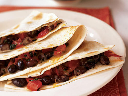 Quesadillas are quick to assemble, but if you're cooking them one at a time on the stove, feeding the whole family could take awhile. That's why we broil all of them at once in this recipe―it takes three minutes total. Add five minutes for the bean filling and two for the corn salsa and you've got a 10-minute meal.