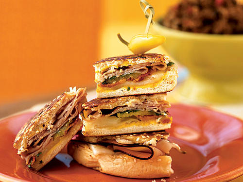 Cuban sandwiches are a great way to deliver big, hearty flavor in a very short time. This recipe includes the traditional mustard, pickle, and Swiss cheese, but uses Hawaiian bread to add a little sweet contrast (if you're more traditional, use Cuban, Italian, or French bread). Then we add bacon for its salty crunch, and toast the sandwiches in garlic oil for even more deliciousness. Add sweet or hot peppers if you like.