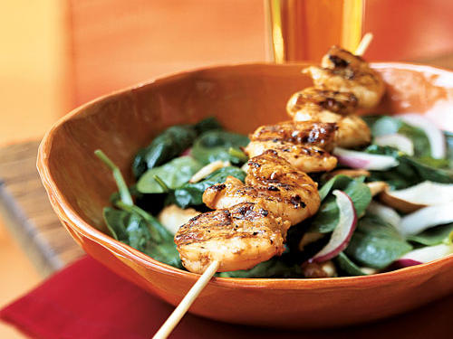 An Asian-flavored vinaigrette with an orange juice kicker is the secret to this simple salad, while ginger and cumin give the shrimp skewers nice spice.