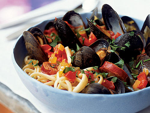 The cuisine of Spain may not be as familiar to most Americans as Mexican, Italian, and Chinese food are. What a shame, as it yields many dishes as delightful and easy as this one. With the briny ocean flavor of mussels, the smoky cured-pork essence of chorizo (use Spanish chorizo, which is less spicy and more smoky than the Mexican version), and the unmistakable Spanish taste and color of saffron, this bowl is a warm savory meal suitable for any day of the week.