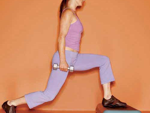 Hold a 5- to 8-pound dumbbell in each hand, and place left foot on a step or low bench. Take a big step back with right leg (at least three feet behind you) as you bend left knee to a 90-degree angle, as shown. Straighten left leg as you bring right leg forward, and touch step with right foot. Perform 8 to 12 repetitions, then switch legs. To increase difficulty: Lift back knee instead of touching step.