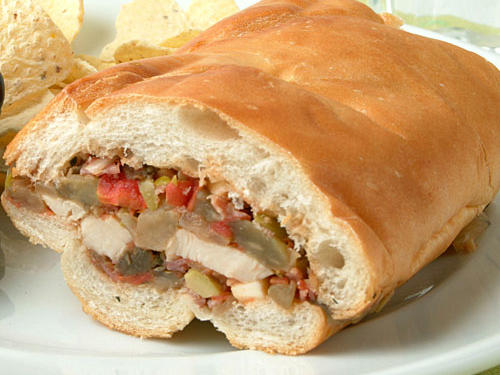 Our Chicken Muffuletta is a lighter take on an old New Orleans favorite. Packed full with chicken, salami, olives, onions, and spices, it's a great make-ahead sandwich for a summer picnic.